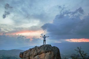 A person stands on top of a cliff. They are feeling happy since starting online therapy in Katy, TX with Barton Counseling.