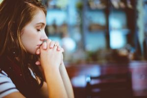 A girl with her eyes closed and hands crossed in front of her face as she considers starting anxiety treatment in Katy, TX with Barton Counseling or in online therapy in Texas for anxiety treatment.