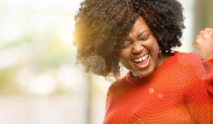 A woman smiles looking triumphant. She is feeling happy after starting depression counseling in Katy, TX with Barton Counseling.
