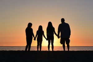 A family of four stands holding hands while looking at the sunset. They are thankful for their family therapist in Katy, TX at Barton Counseling Services. You can get anxiety therapy in Katy, Texas too! 77494.