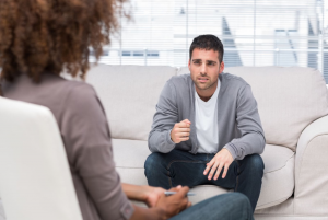A young man discusses his troubles during anxiety therapy in Katy, TX at Barton Counseling. Get help for your anxiety symptoms and more with online therapy in Texas, too.