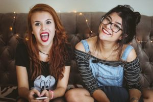 Two teenage girls sit next to each other smiling. They are feeling much happier after beginning to see a teen counselor with Barton Counseling Services. You too can get teen counseling in Katy, Texas 77494.