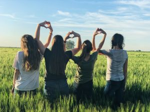 Four teenage girls stand side by side making hearts with their hands. They have started counseling for teens in Katy, TX with teen counselor Melissa Barton at Barton Counseling Services.