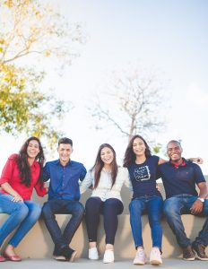 A group of 5 friends sit together smiling. They are feeling happy since starting counseling for failure to launch syndrome in Houston, TX with Barton Counseling Services.